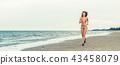 Attractive woman runs on sand beach in summer. 43458079