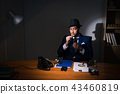 Detective sitting in dark room in vintage concept 43460819