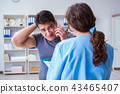 Young man visiting female traumatologist with black eye  43465407