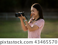woman looking through photos on camera to check 43465570