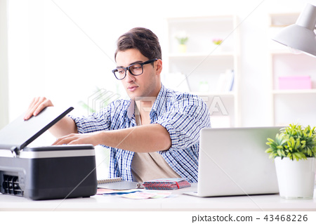 Young man employee working at copying machine in the office  43468226