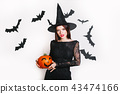 happy woman in black witch halloween costumes with pumpkin on party over white background 43474166
