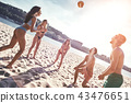 Time with friends. Group of young people playing volleyball on the beach 43476651