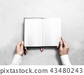 Hand holding blank opened book mock up with white pages. 43480243