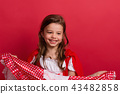 A small girl in Little Red Riding Hood costume in studio on a red background. 43482858
