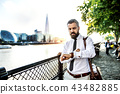 Hipster businessman with laptop bag walking by the river in London, checking the time. 43482885