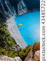 Figure of a parachutist skydiver with orange parachute against a blue lagoon of Myrtos Beach 43485722