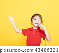 happy little girl singing on yellow background 43486321