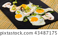 Cooked fried quail eggs and champignons mushrooms at plate on table 43487175