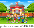 Happy school children standing in front of school  43494186