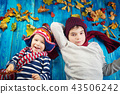 Children in hats and scarfs and maple leaves on blue background 43506242