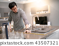 Asian man using tape measure on kitchen counter 43507321