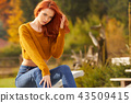 woman is sitting on the terrace in front of the house. Autumn sc 43509415