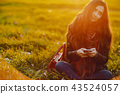 brunette girl using phone while at the park 43524057