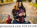 brunette girl using phone while at the park 43524148
