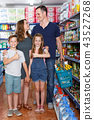 Parents with children holding cart with food 43527268