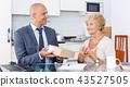 Sales representative passing box to woman 43527505