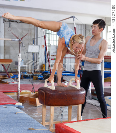 Woman in bodysuit exercising action at vaulting hourse in gym, man helping 43527589