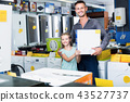 Smiling dad with daughter in household store 43527737
