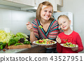 Happy mother and daughter eating vegetable salad 43527951