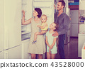 family of four shopping new refrigerator in home appliance store 43528000