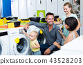 Adult family with kids choosing washing machine 43528203