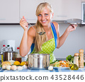 Woman cooking vegetables. 43528446