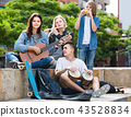 Portrait of four teenagers playing music together outdoors 43528834
