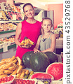 Woman with daughter buying bananas 43529768
