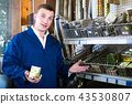 man seller wearing uniform having metal furniture in hands in store 43530807