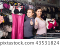 two female customers holding bras and panties in hands in underwear store 43531824