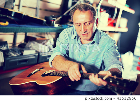 male is repairing music instruments 43532956