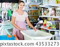 Smiling pregnant woman choosing baby bath in kids store 43533273