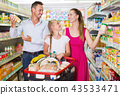Happy family standing with purchases in shopping cart 43533471