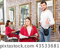 Portrait of man professional hairdresser near woman client with magazine in salon 43533681