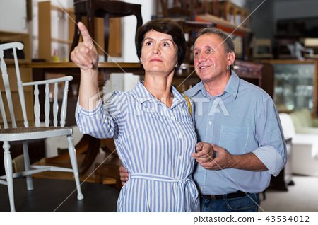 mature woman with her positive husband who are satisfied of buying furniture in antique store 43534012
