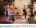 Waitress offering a cup of coffee in cafe. cappuchino 43535313