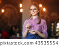 Portrait of a beautiful friendly waitress in glasses with notepapers and pen ready to take your 43535554