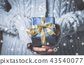 woman holding gift box in winter 43540077
