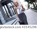 Attractive young woman walking outdoors 43545296