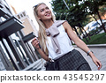 Attractive young woman walking outdoors 43545297