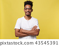 Close up portrait of a happy african american man posing with arms crossed on isolated yellow 43545391