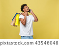 young man with shopping bags talking on smart phone isolated on yellow background 43546048