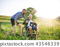 An adult hipster son with senior father in wheelchair on a walk in nature at sunset. 43546339