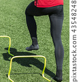 Behind view of athlete stepping over mini hurdle 43548248
