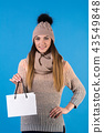 The girl is dressed in a knitted warm sweater and hat with a white gift bag 43549848