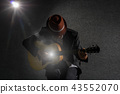 Musician playing the guitar on spot light background, musical concept 43552070