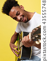 Young handsome African American retro styled guitarist playing acoustic guitar isolated on yellow 43555748