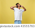 Young African American man wearing headphone and enjoy music over yellow gold Background 43555763