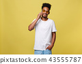 Portrait of cool young black guy talking on cellphone. Isolated on yellow background 43555787